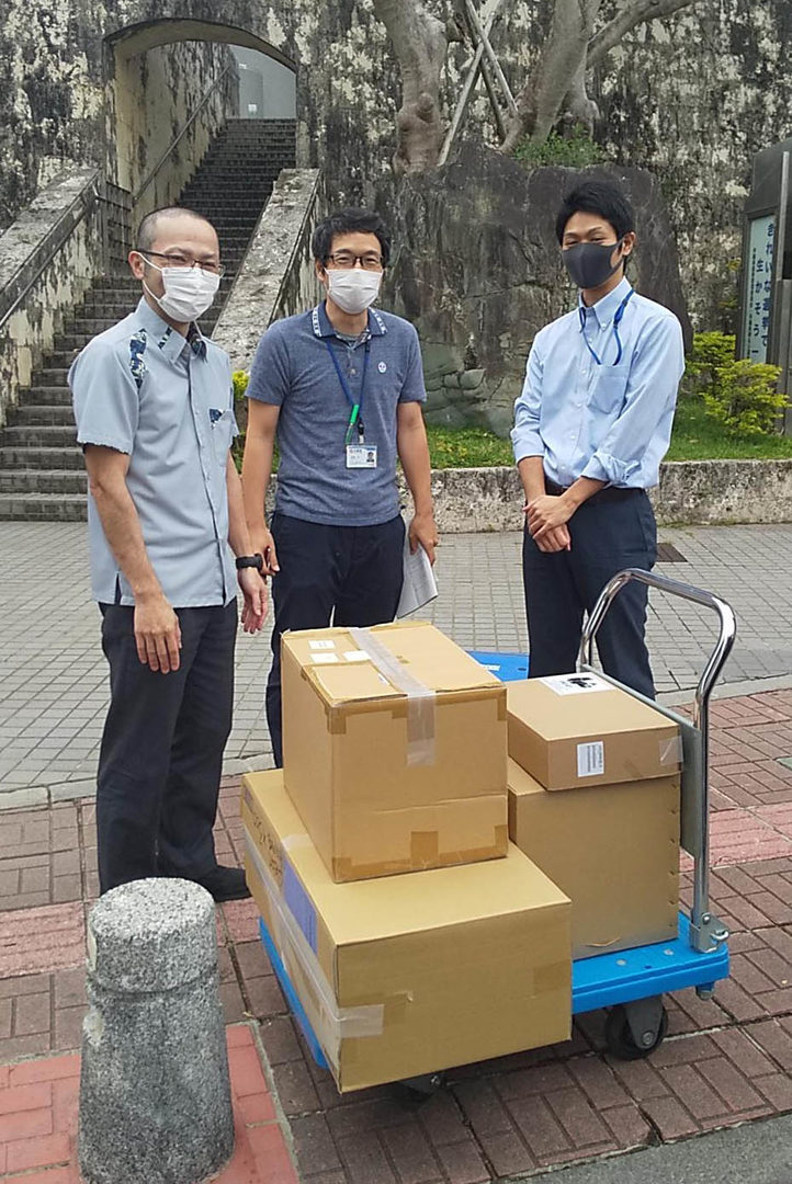 Three men standing next to boxes at the Okinawa Prefectural Government Office.