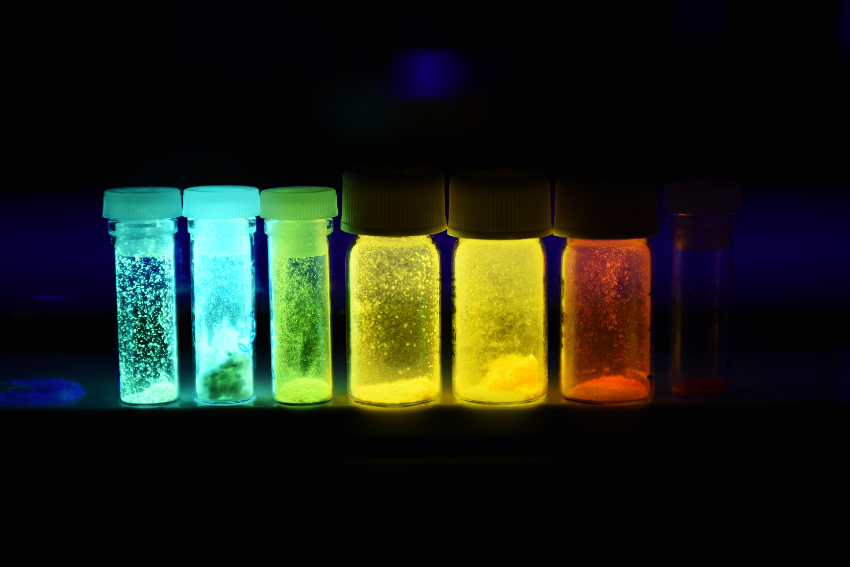 錯体化学・触媒ユニットが合成した光輝性化合物が紫外線の下で光を放つ様子