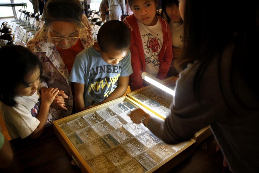 Hiroko Chibana looks at preserved ants with her grandchildren.