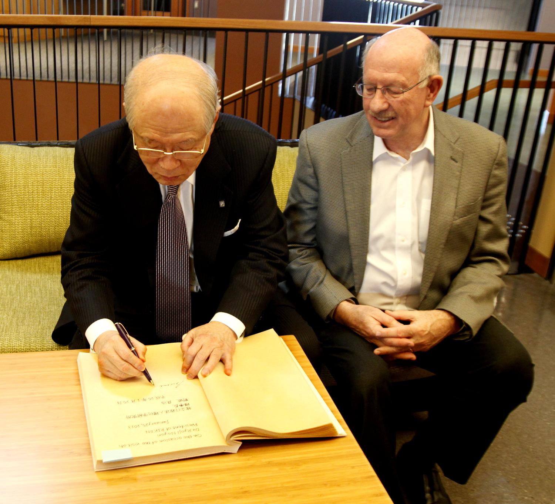 OISTのご芳名帳にサインをする理化学研究所理事長でノーベル賞受賞者の野依良治博士