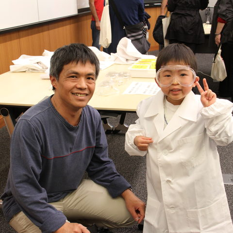 Children put on lab coats and eye protection to look like scientists