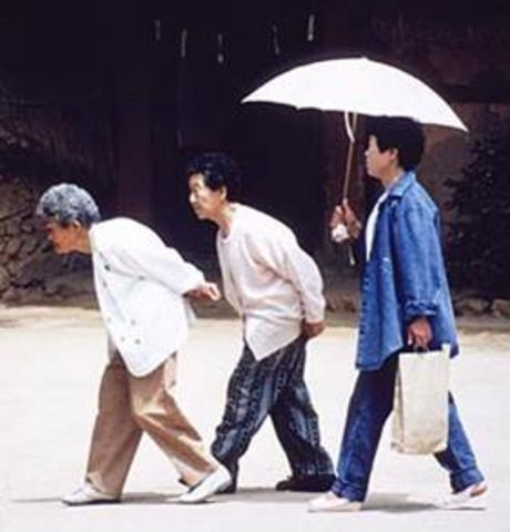 Three old women walking, the first two crouched over