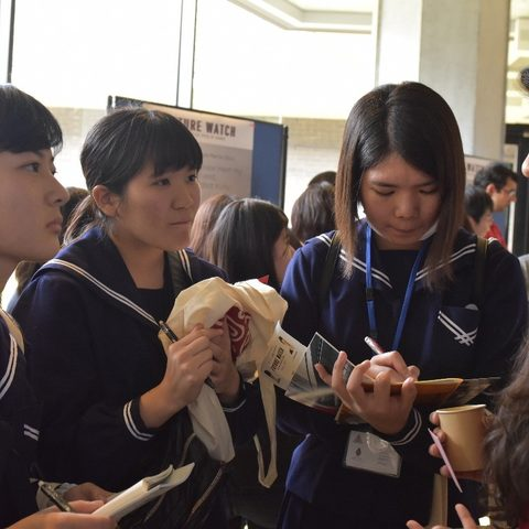 Pravini Wickramanayake from APU (right), speaks with Nago High School students at the 'Future Watch' poster session