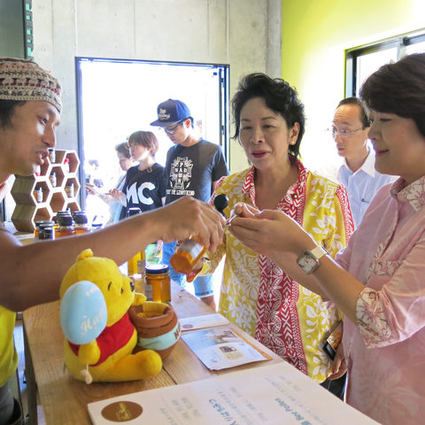 Minister Aiko Shimajiri and lawmaker Natsumi Higa tasting local honey