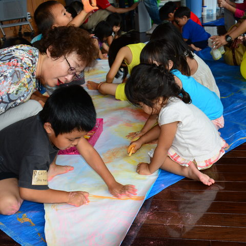 Visitors from Onna Village decorate segments of a mural depicting a life-size humpback whale.