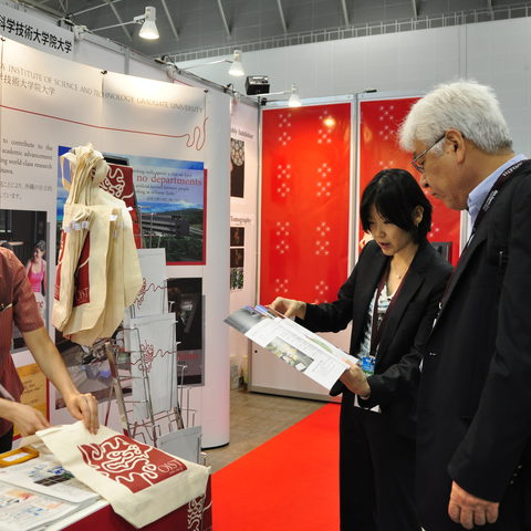 Ms. Nishimura (right) and Ms. Lee Nakasone attend a visitor to the OIST booth